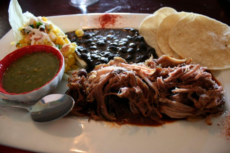 Pork carnitas with black beans, corn tamale, and green and red chile sauces