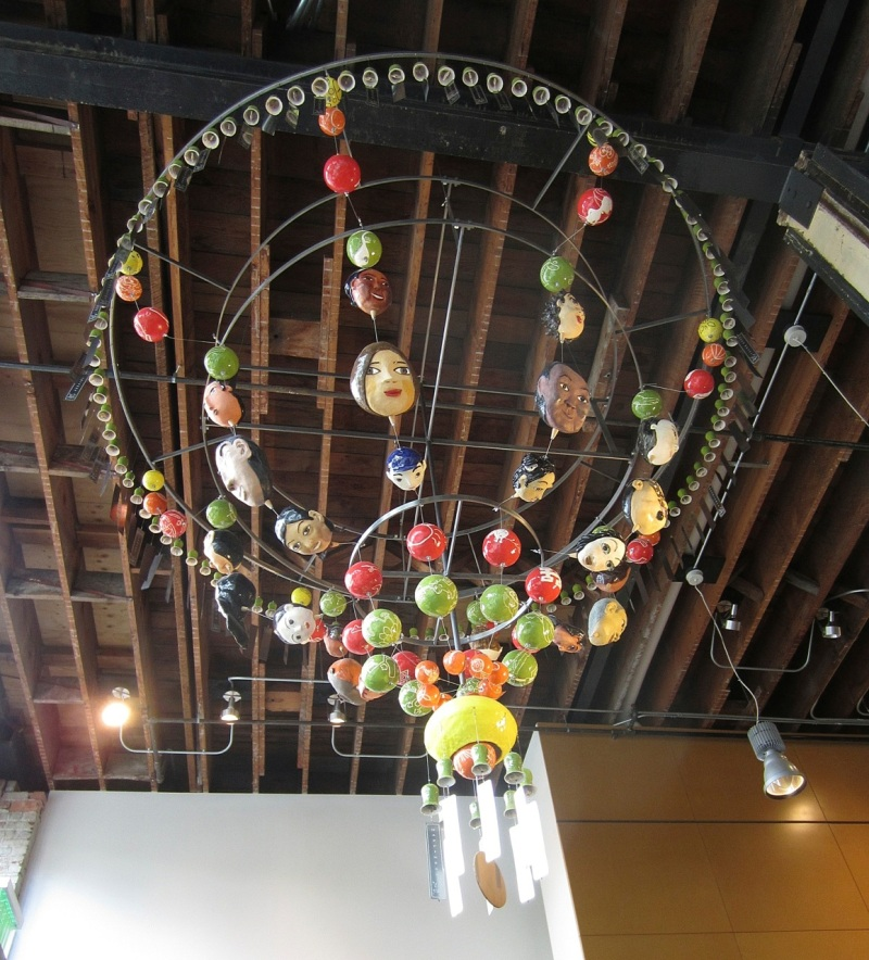 """Sweet Hello,"" chandelier of wind chimes, ornaments and masks"