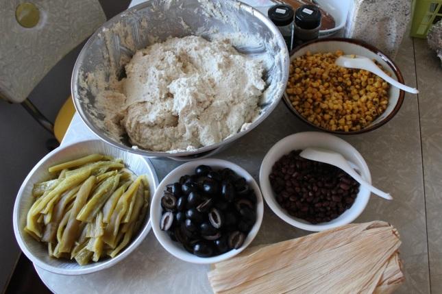 Masa dough, roasted corn, black beans, olives, roasted chiles, corn husks
