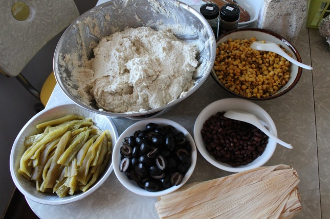 Masa dough, roasted corn, black beans, olives, roasted chiles, corn husks
