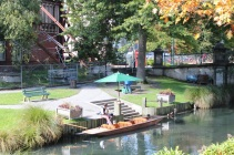 A boater waits by his flat-bottomed boat to take passengers punting on the Avon