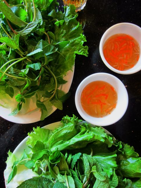 Bánh khọt and bánh xeo are wrapped with lettuce leaves and herbs, dipped in nuoc cham